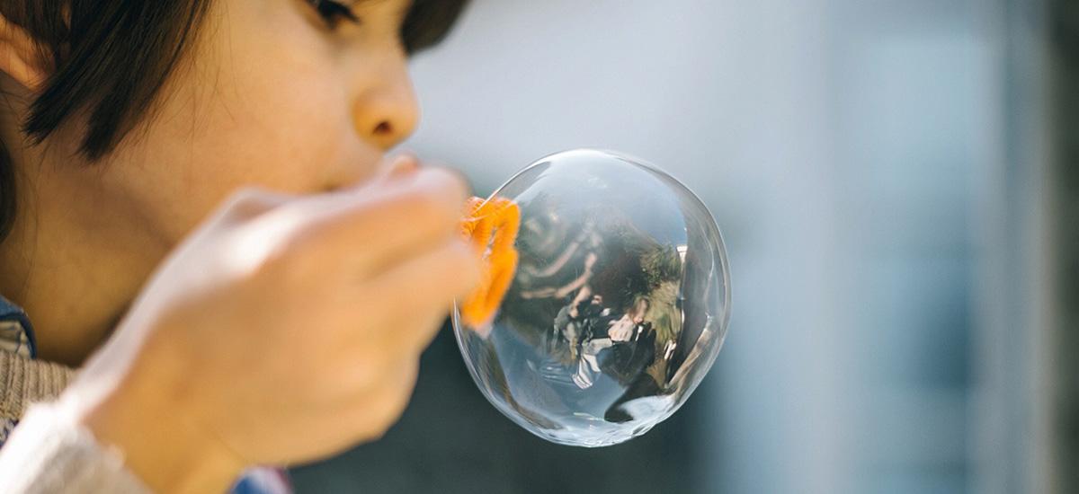 Child blowing bubble.